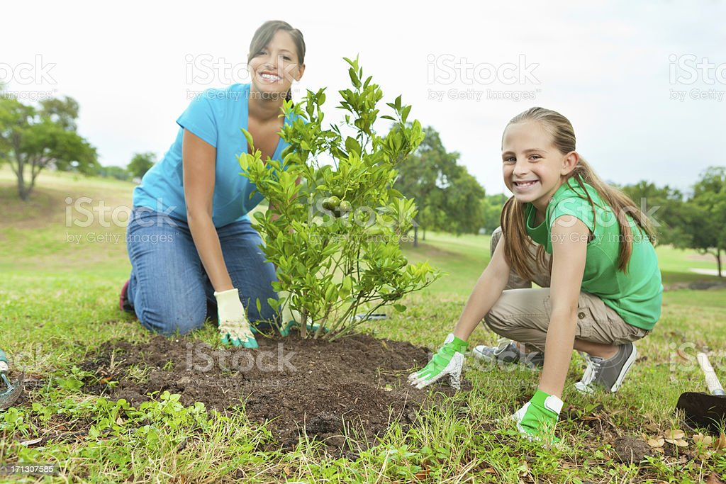 Happy mom and daughter planting trees on Arbor Day stock photo