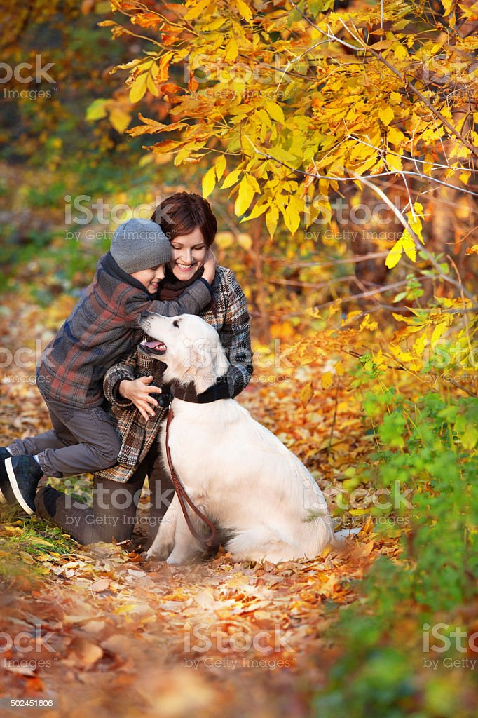 Happy mom and her son with dog stock photo