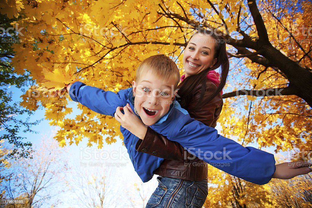 happy mom and son are playing in the autumn park royalty-free stock photo