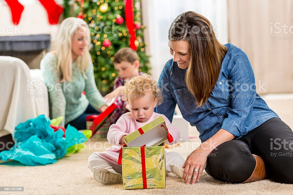 Happy mom opens gifts with children on Christmas morning stock photo
