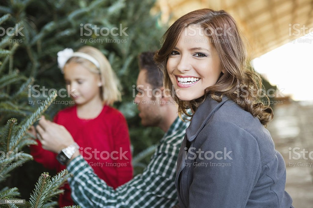 Happy mom smiles as husband and daughter choose Christmas tree royalty-free stock photo