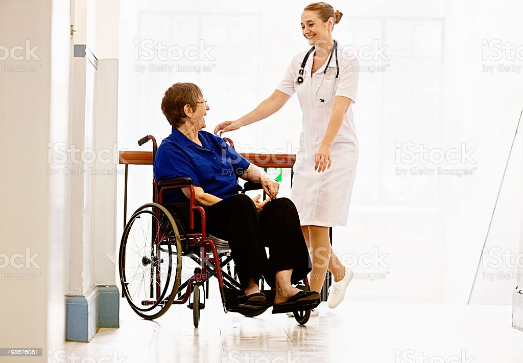 In a hospital or nursing home, a smiling nurse interacts with a...