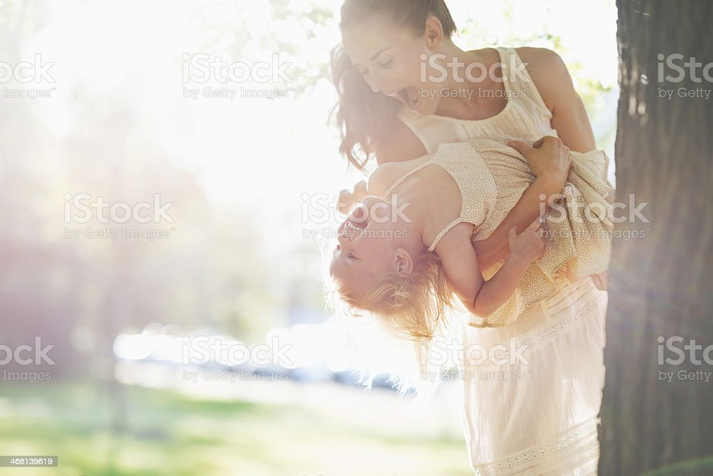 happy mother and baby having fun near tree stock photo