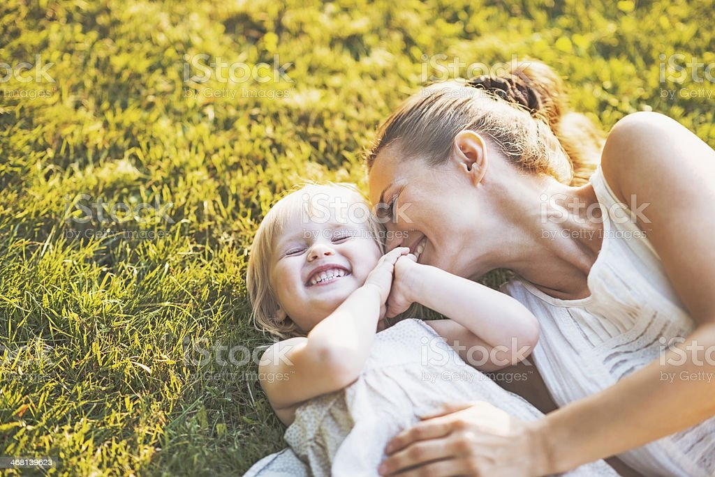 happy mother and baby laying on meadow stock photo