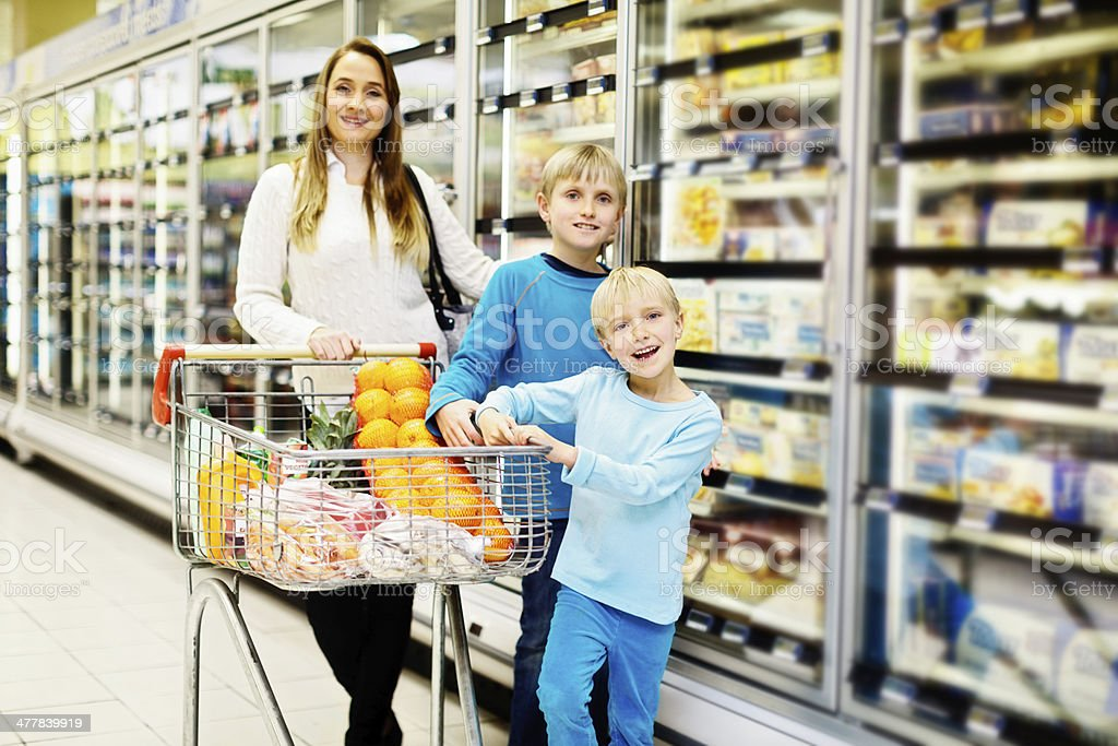 Happy mother and children shopping in supermarket royalty-free stock photo