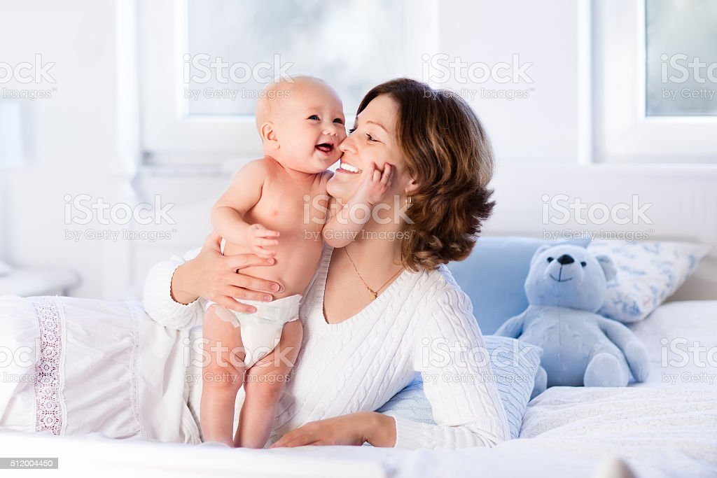 Happy mother and cute baby on a white bed stock photo