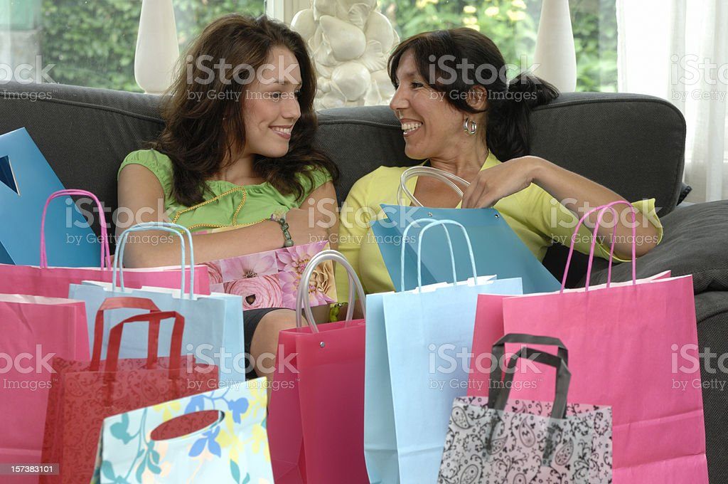 happy mother and daughter after shopping on sofa royalty-free stock photo