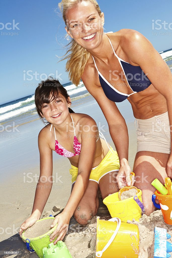 Happy mother and daughter building a sandcastle stock photo