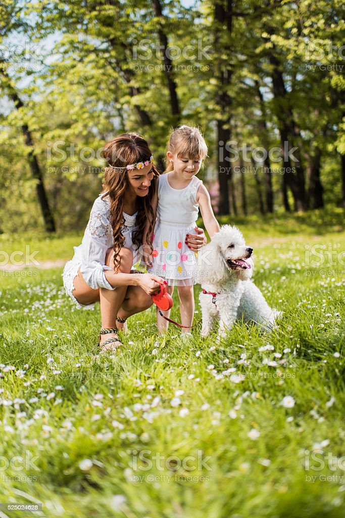 Happy mother and daughter enjoying with their poodle during sprigtime. stock photo