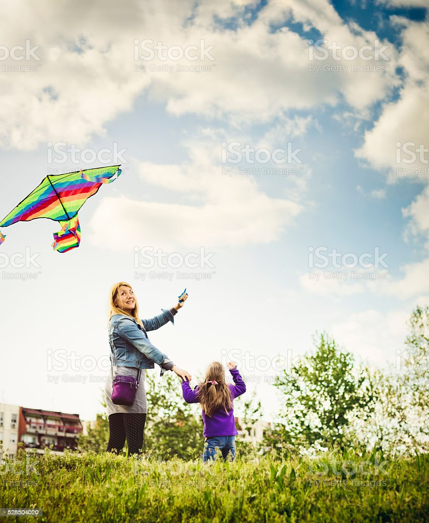 Happy mother and daughter flying kite in nature stock photo