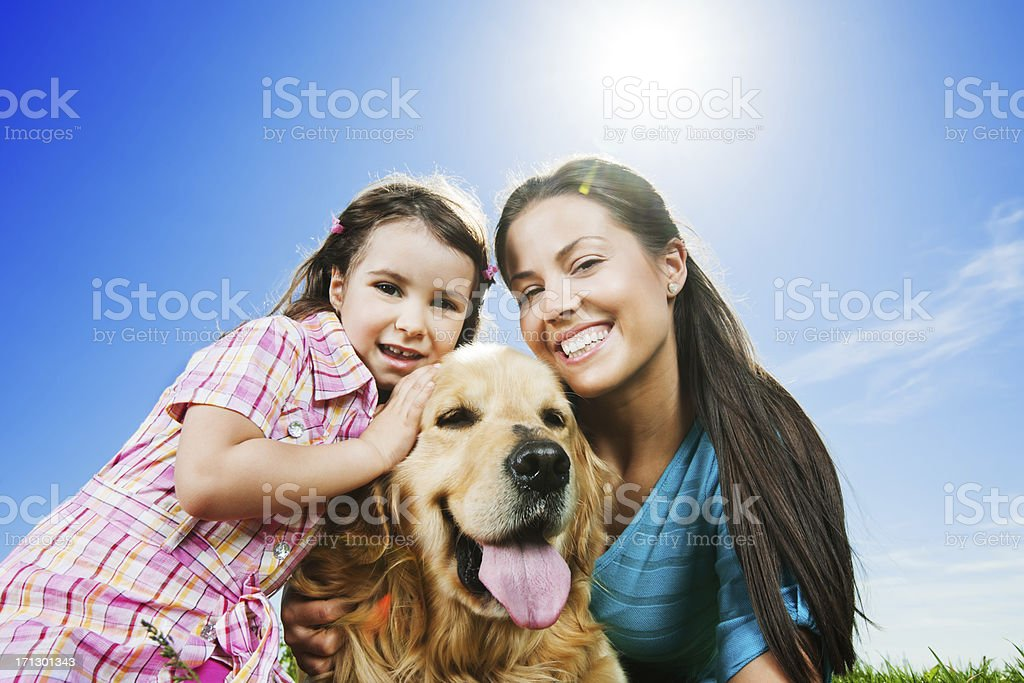 Happy mother and daughter in park with their dog. royalty-free stock photo