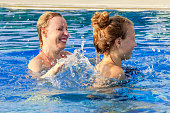 Happy mother and daughter in the swimming pool