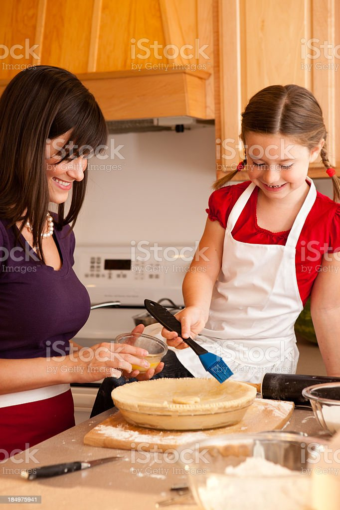 Happy Mother and Daughter Making Cherry Pie in Kitchen stock photo
