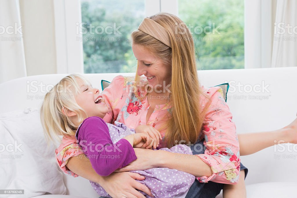 Happy mother and daughter on the couch stock photo
