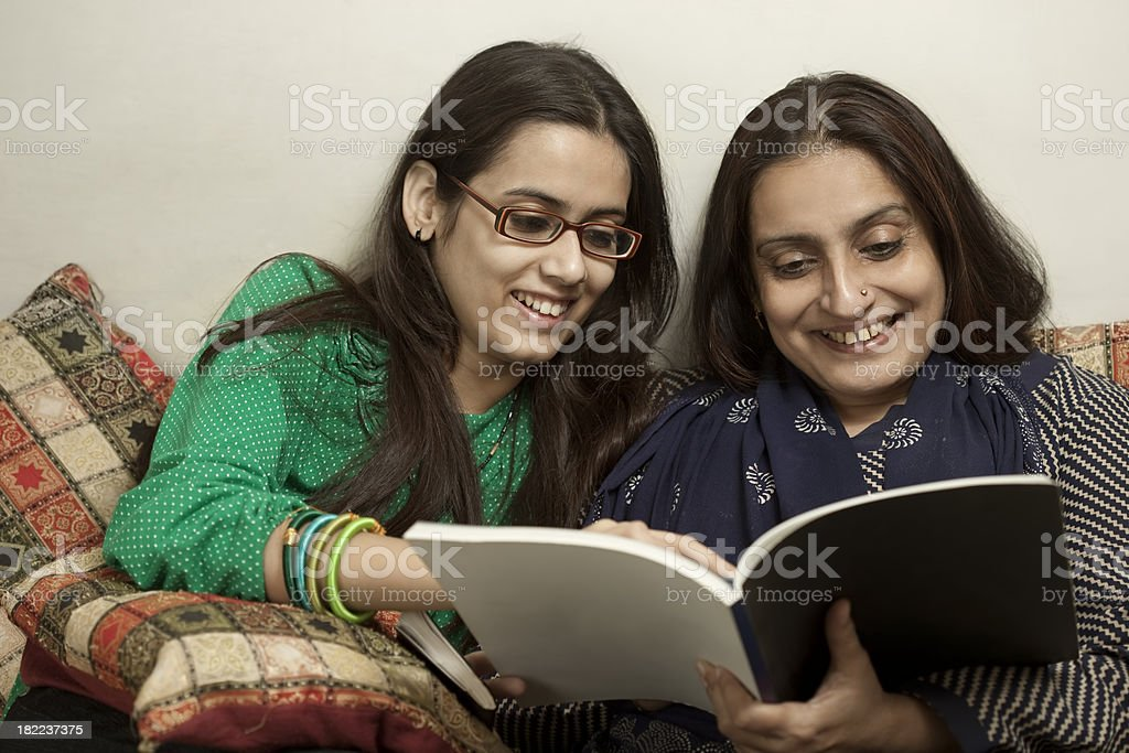Happy mother and daughter reading a book stock photo