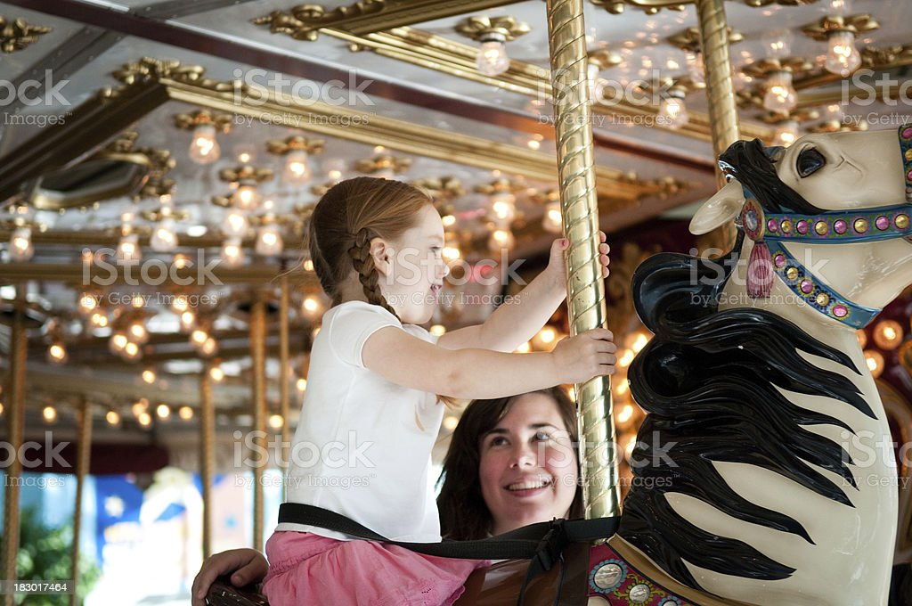 Happy Mother and Daughter Riding Carousel Horse stock photo