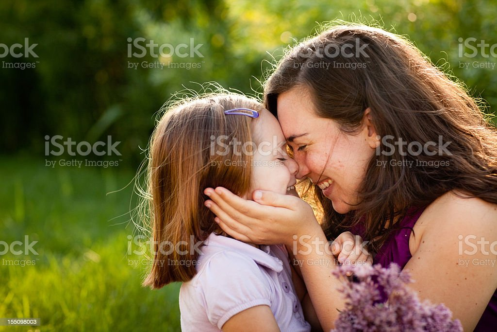 Happy Mother and Daughter Smiling While Touching Noses Outside royalty-free stock photo