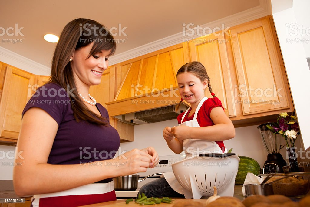 Happy Mother and Daughter Snapping Beans in Their Kitchen royalty-free stock photo