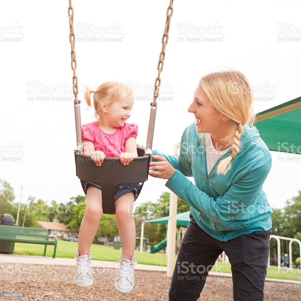 Happy mother and daughter swinging at the playground stock photo