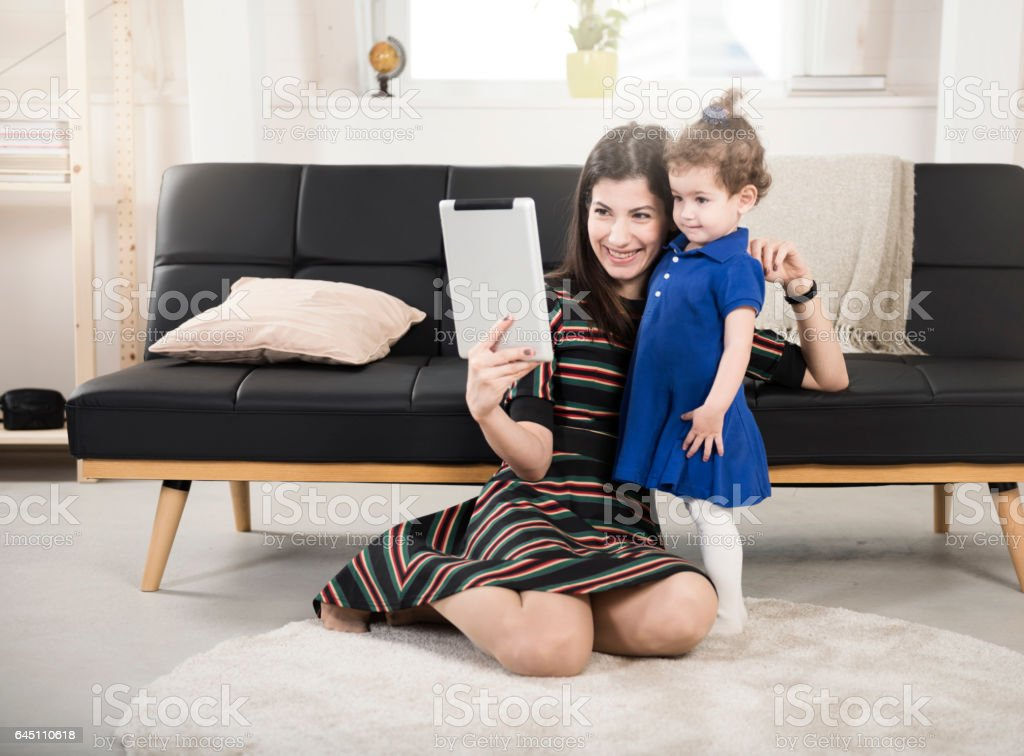 Happy mother and daughter taking selfie with digital tablet at home stock photo
