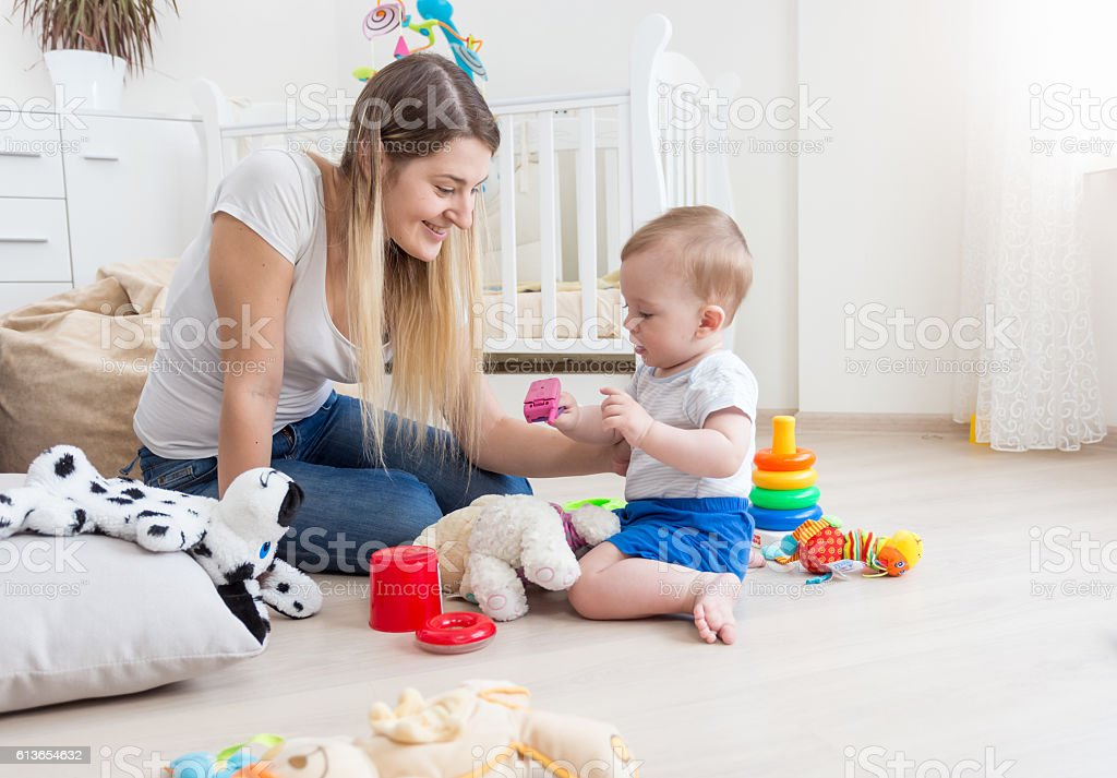Happy mother and her baby playing with to cell phone stock photo