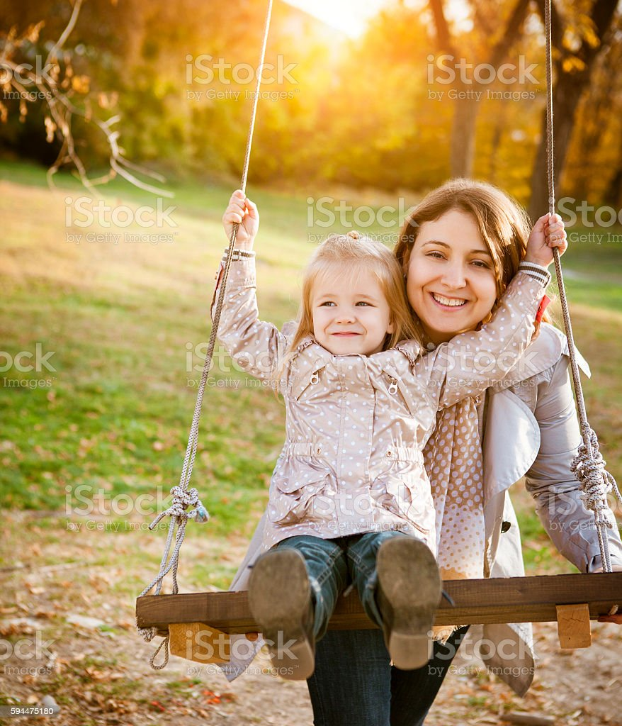 Happy mother and her little baby swing stock photo