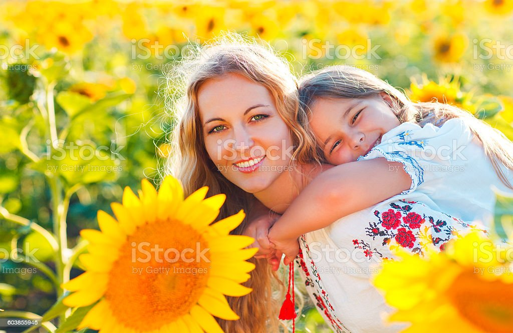 Happy mother and her little daughter in the sunflower field stock photo