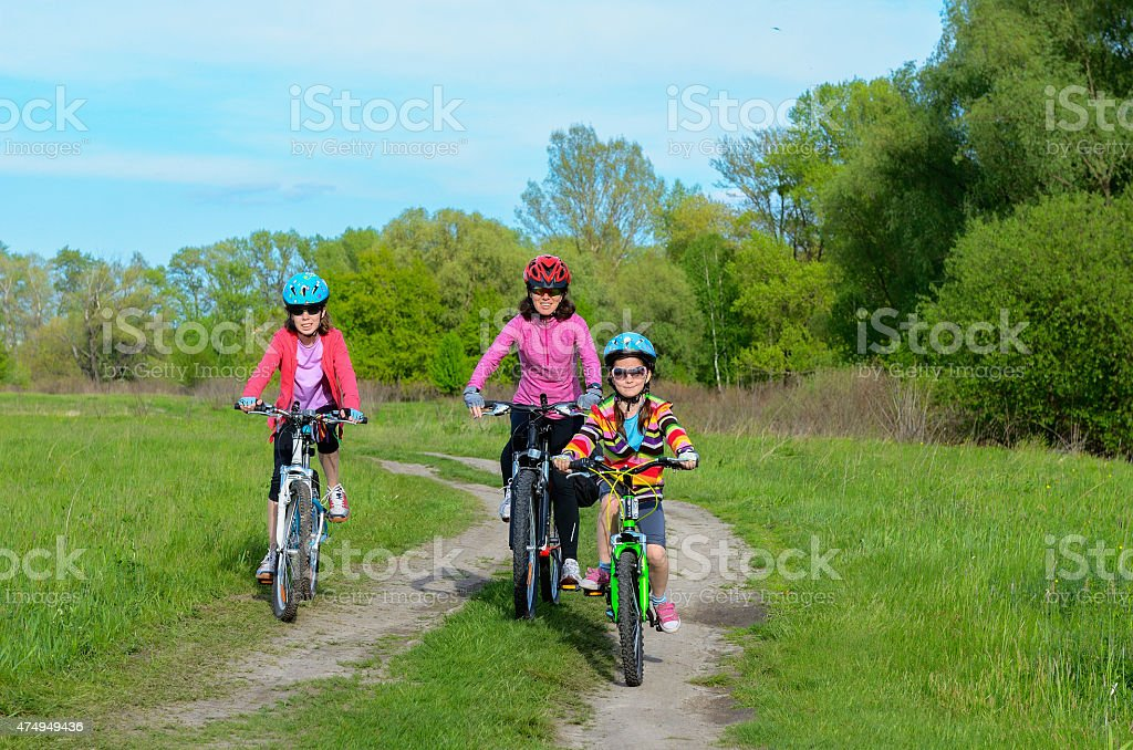 Happy mother and kids on bikes cycling outdoors, family sport stock photo