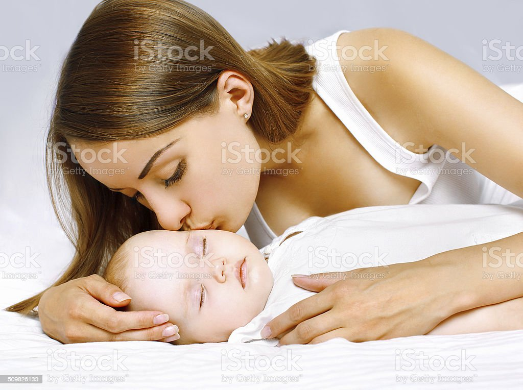 Happy mother and sleeping baby in the bed stock photo