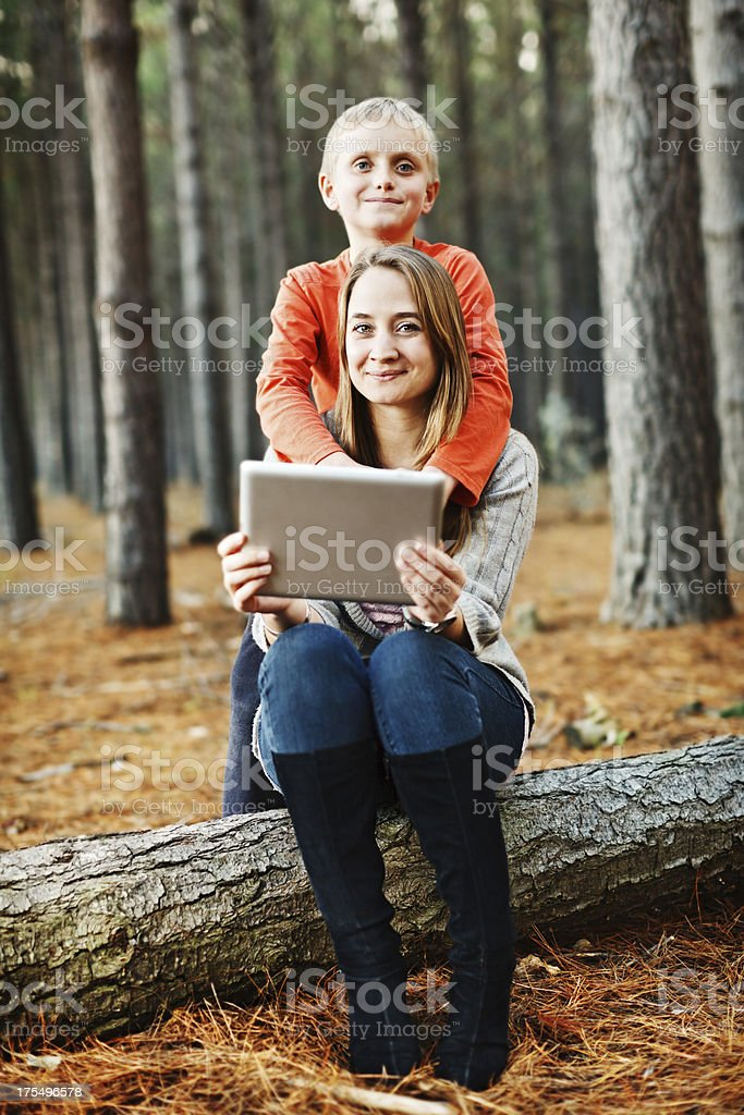 Happy mother and son in forest with new tablet pc stock photo