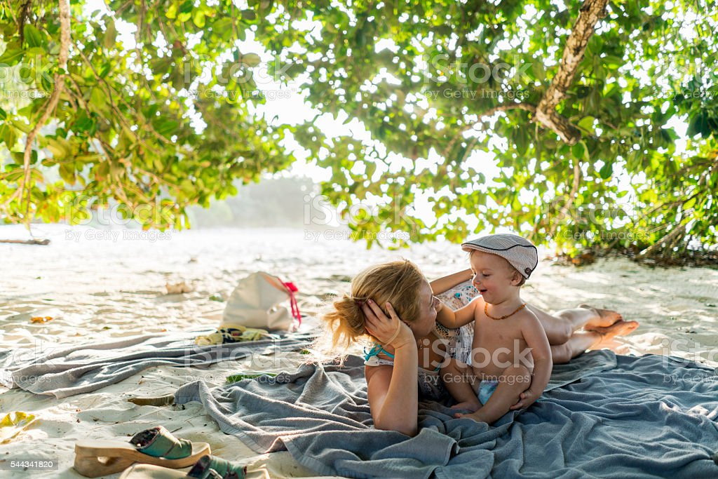 Happy mother and son relaxing in a shade at beach. stock photo
