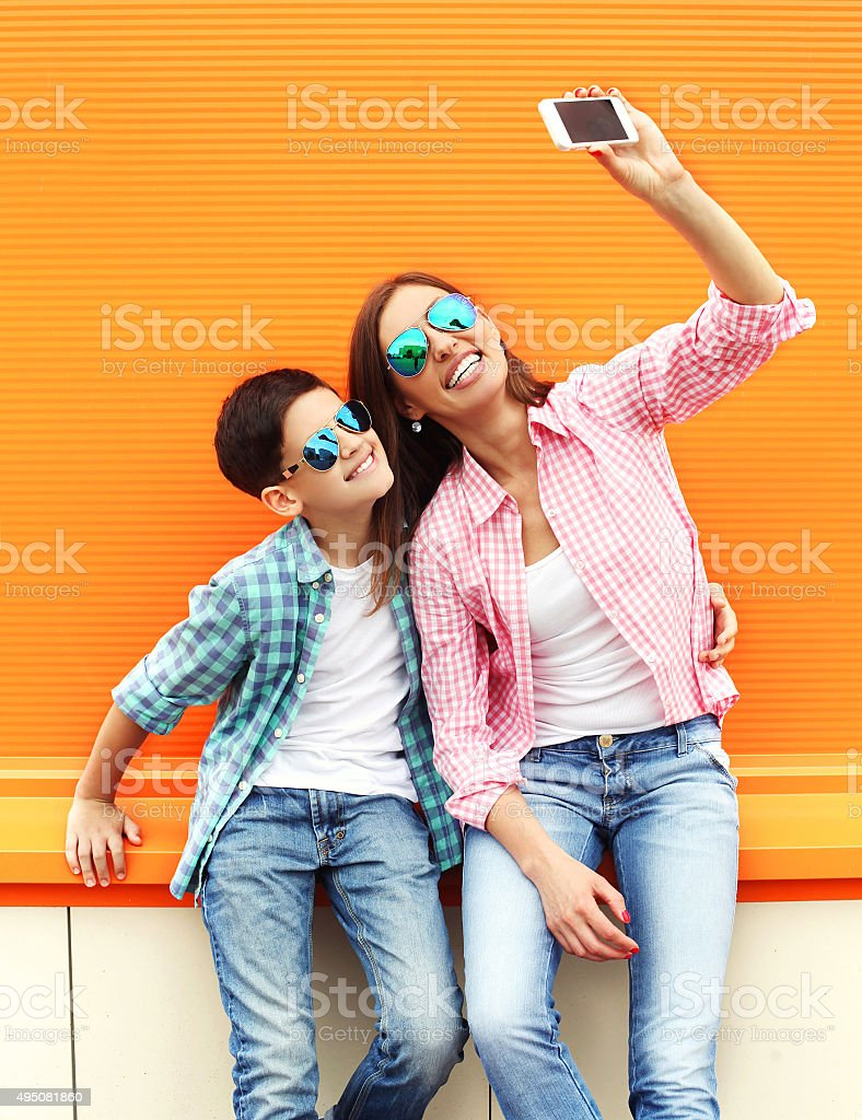 Happy mother and son taking picture self portrait on smartphone stock photo