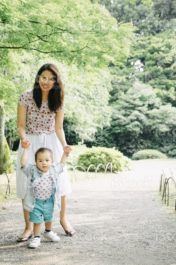 Happy mother and son walking together outdoors in a park stock photo