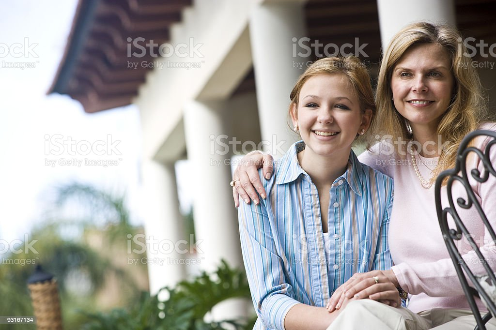 Happy mother and teenage girl sitting together outdoors royalty-free stock photo