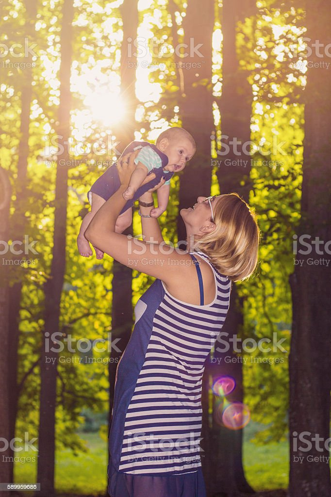 Happy mother and toddler - baby outdoors at sunset stock photo
