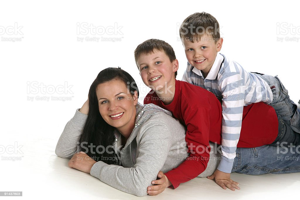 Happy mother and two sons lying down the floor. royalty-free stock photo