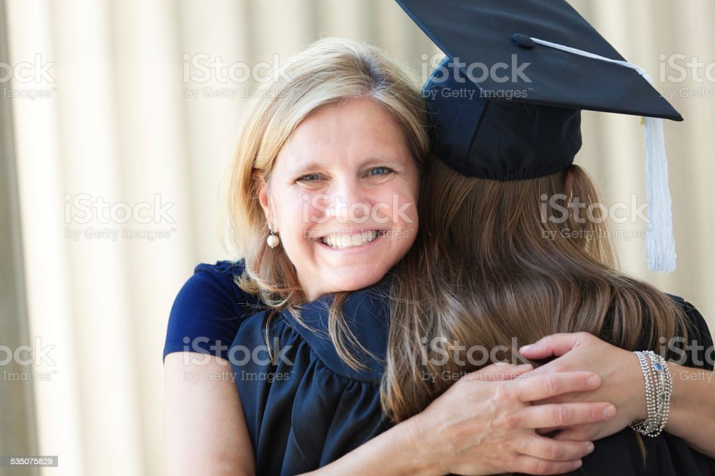 Happy Mother Congratulating Hugging Daughter in University Graduation Ceremony stock photo