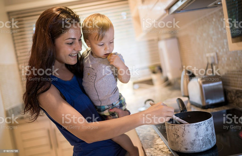 Happy mother cooking with her son in the kitchen. stock photo