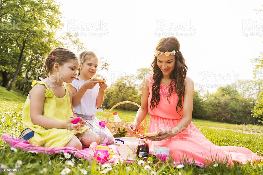 Happy mother enjoying with her two daughters on a picnic. stock photo