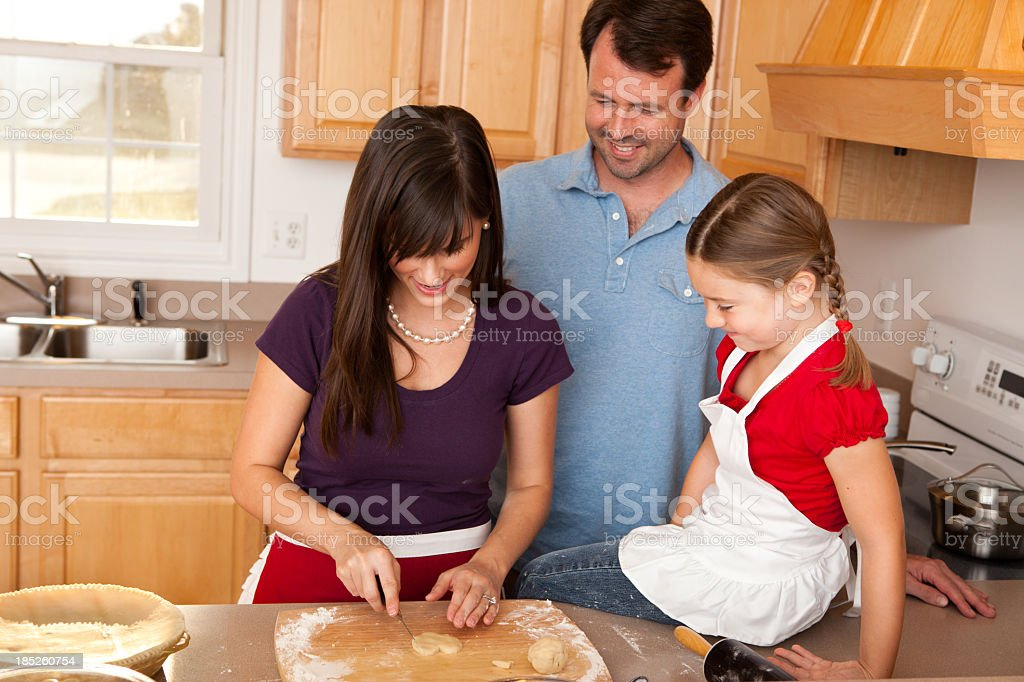 Happy Mother, Father, and Daughter Baking Pie in Kitchen royalty-free stock photo