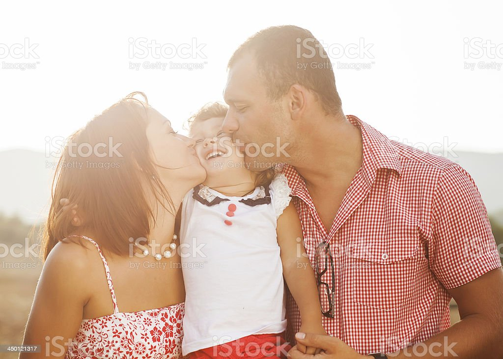 Happy mother, father and daughter in sunset royalty-free stock photo