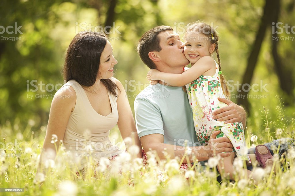 Happy mother, father and daughter in the park royalty-free stock photo