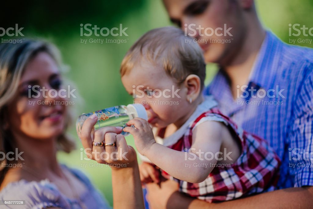 Happy mother, father and daughter in the park stock photo