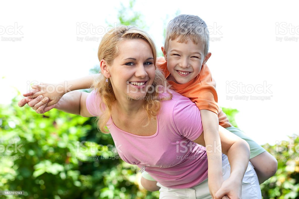 Happy mother giving a piggyback to her son royalty-free stock photo