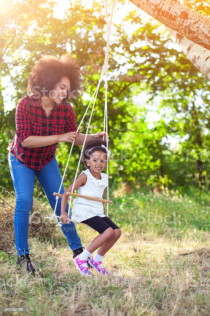 Happy mother having fun with your child on a swing stock photo