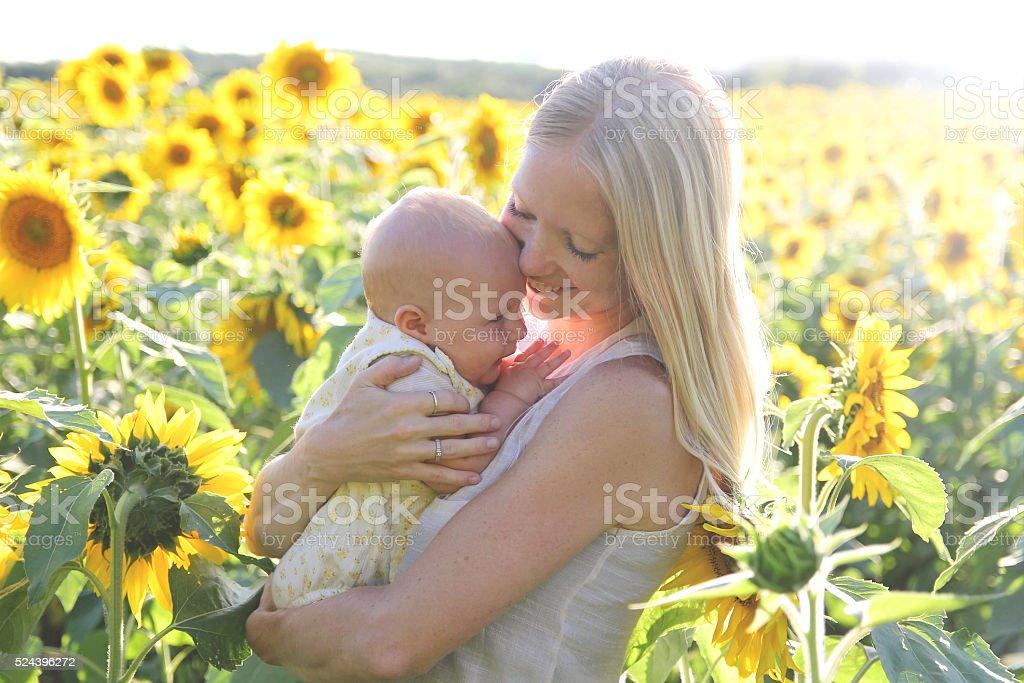 Happy Mother Hugging Baby Daughter in Flower Meadow stock photo
