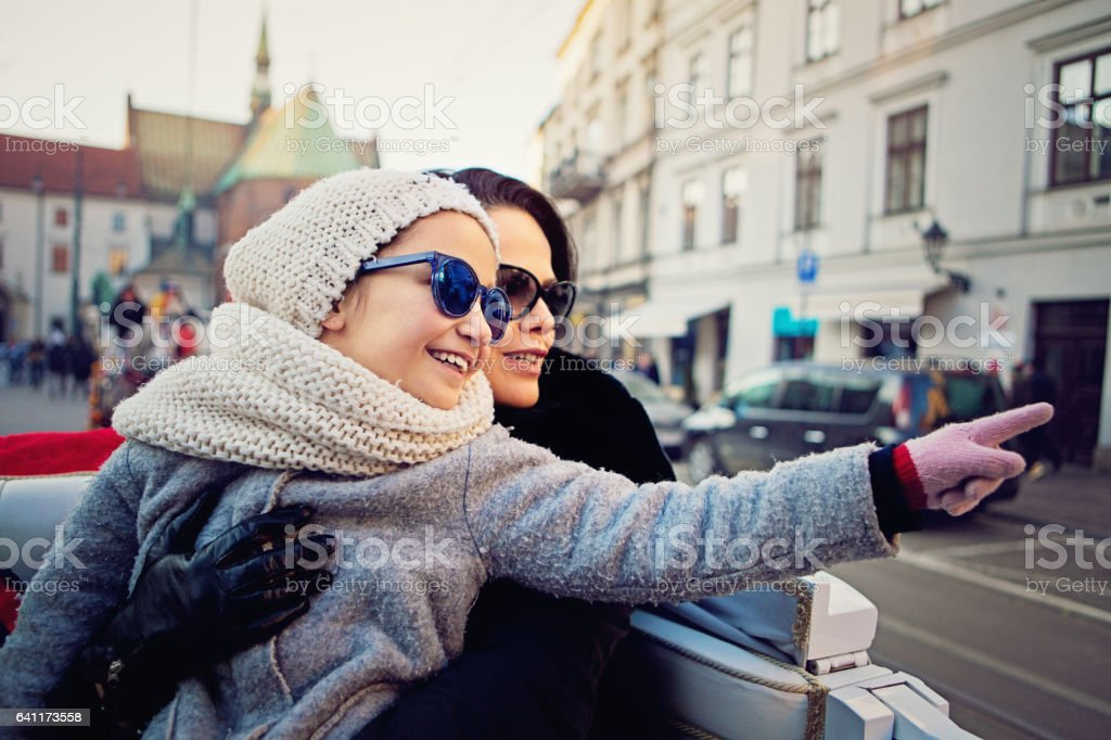 Happy mother is hugging her daughter in a horse carriage stock photo
