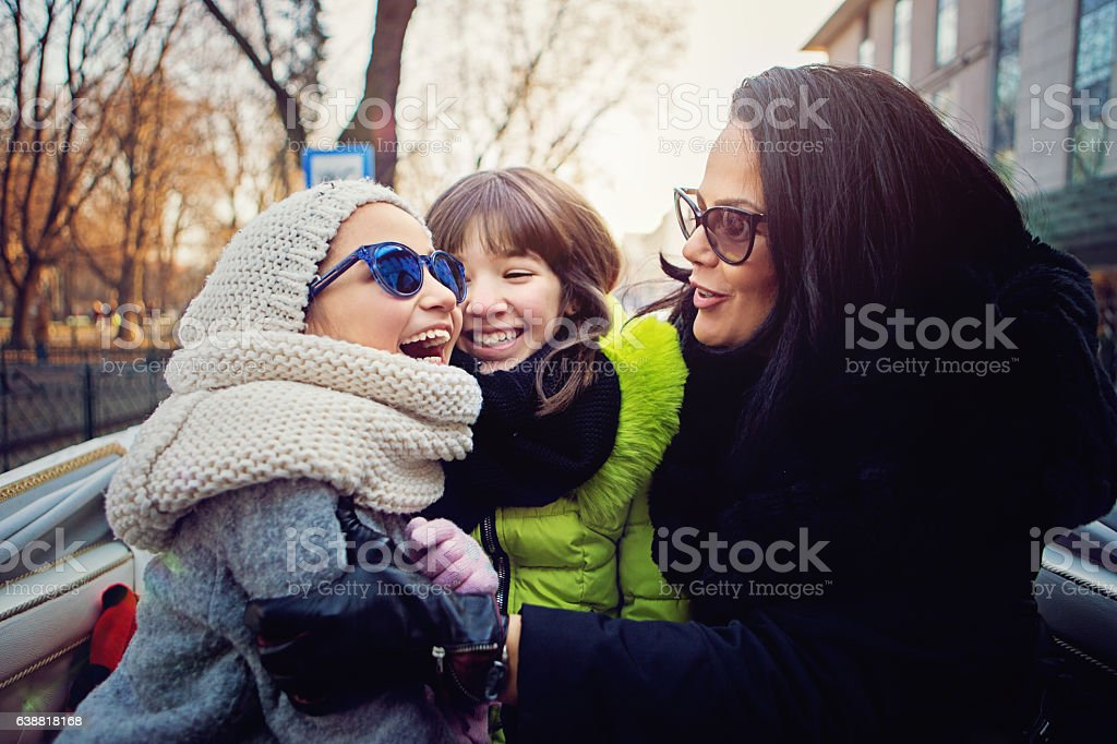 Happy mother is hugging her daughters in horse carriage stock photo
