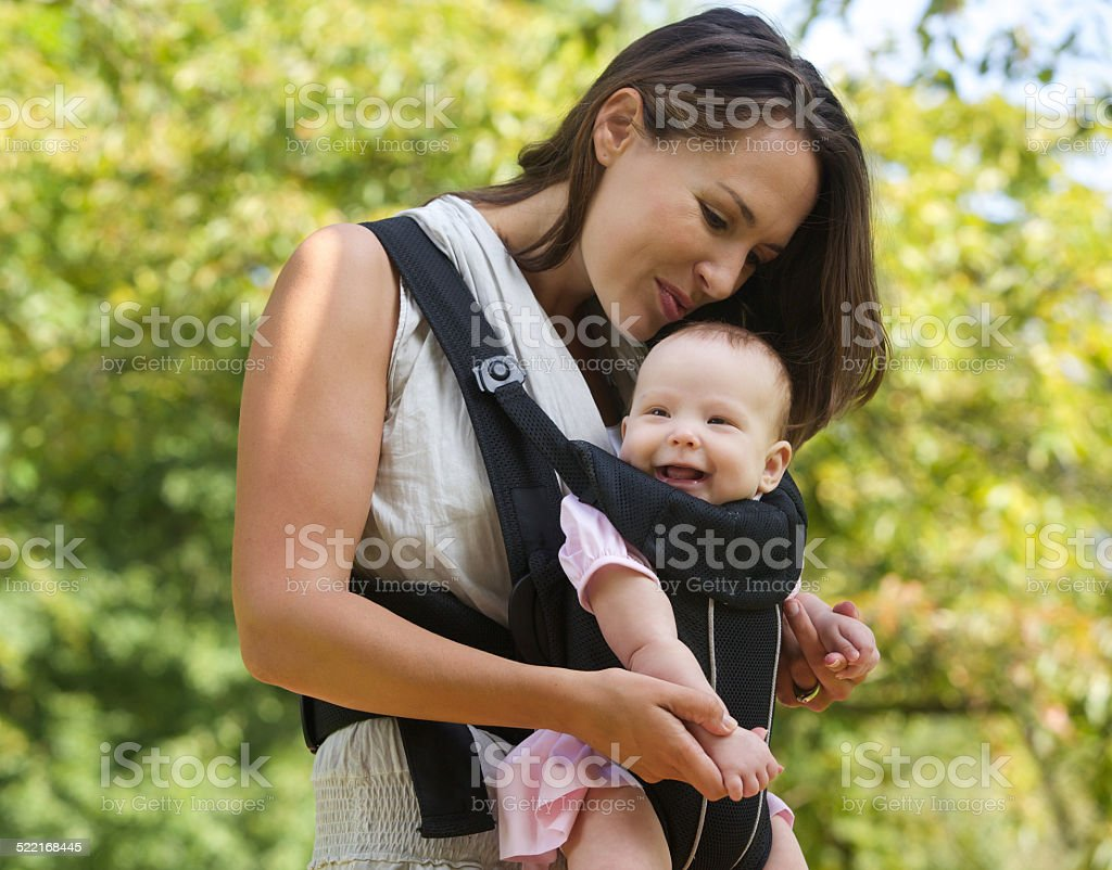 Happy mother kissing baby on the head stock photo