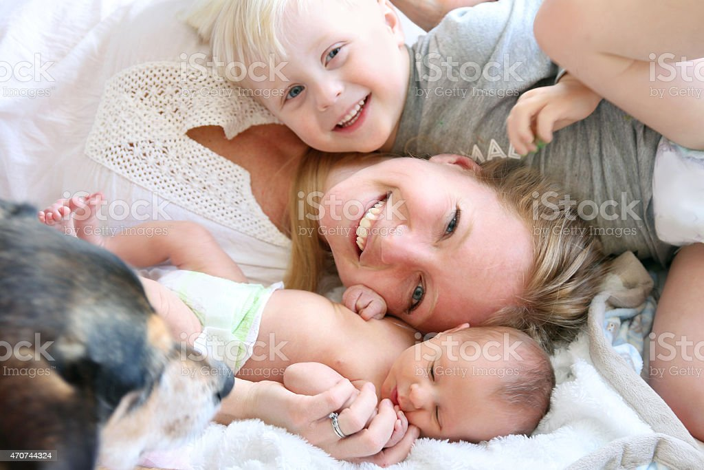 Happy Mother Laying in Bed with Son and Newborn Baby stock photo
